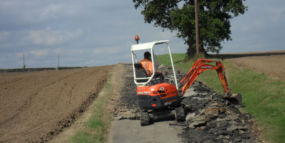 a road surface being broken up by a digger