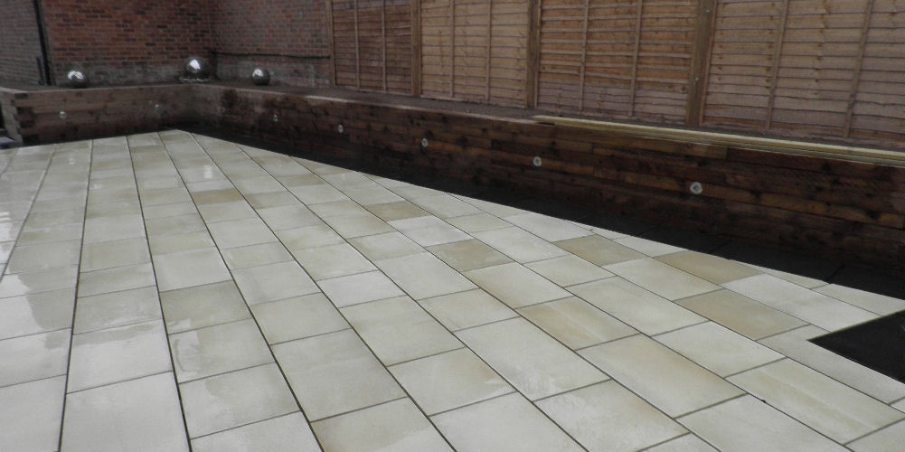 a fully landscaped garden including slabs, fencing and a wall